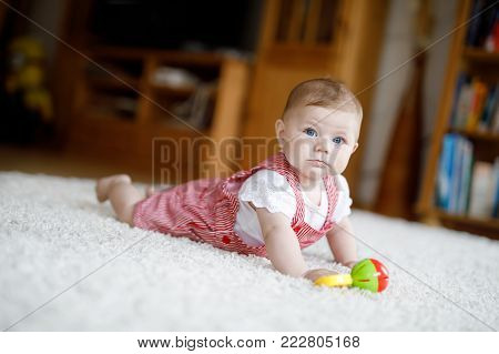 Cute baby playing with colorful rattle education toy. Lttle girl looking at the camera and crawling. Family, new life, childhood, beginning concept. Baby learning grab