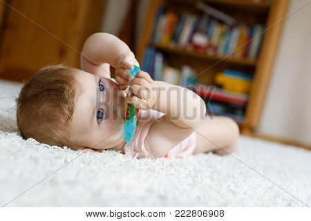 Adorable baby girl playing with educational toys in nursery. Happy healthy child having fun with colorful different toys at home. Cute baby learning grab and hold things and toys