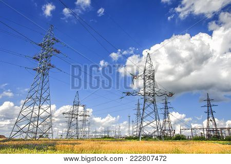 High-voltage power lines in field with golden wheat and blue beautiful sky with white clouds. Landscape of powerful electric lines on bright summer day