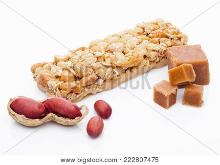 Caramel protein cereal energy bar with peanuts on white background