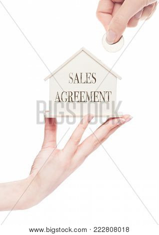 Female hand holds wooden house model and hand holding the coin with conceptual text. Sales Agreement