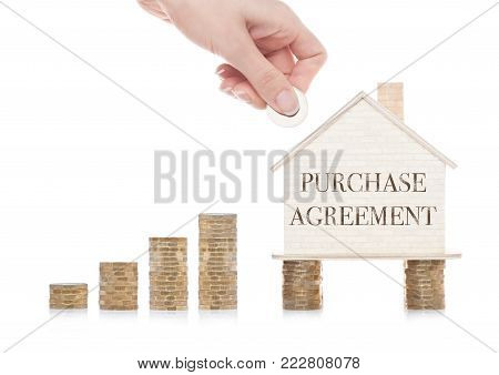 Wooden house model standing on coins and hand holding the coin with conceptual text. Purchase Agreement