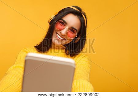 Cheerful young hispanic woman taking a selfie on yellow background. Colorful portrait of girl smiling and making a picture of herself