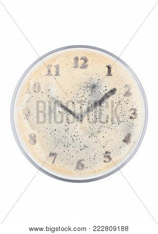 Glass of stout beer top with clock shape on white background top view