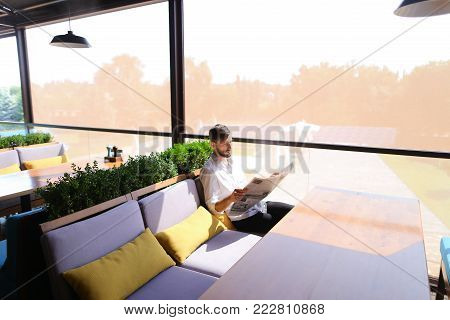 Clever handsome man finding job vacancy in newspaper and enjoying with good result at table. Young male person looks intelligent in white shirt with beard. Concept of occupation search and reading public press for job.