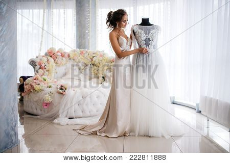 A beautiful bride in a silk night dress admires her wedding dress in the boudoir room. Large white bed decorated with flowers on the background. Wedding morning