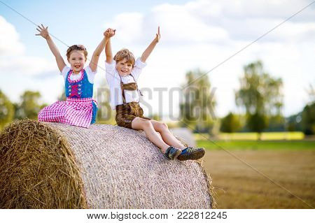 Two kids, boy and girl in traditional Bavarian costumes in wheat field. German children sitting on hay bale during Oktoberfest. Siblings play at hay bales during summer harvest time in Germany