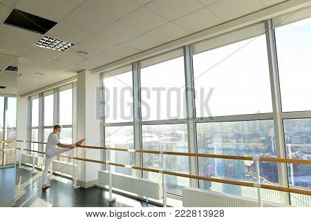 Journalist making successful attempt of standing on hands using ballet barre, tattooed fair-haired guy rejoicing at small win in sport gym. Barefoot boy wearing white T-shirt and trousers. Concept of sportswear, spacious hall or individual trainings
