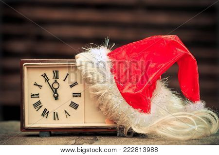 Old hours and Santa Claus cap. New Year's concept