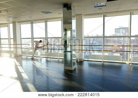 Male dancer doing leg stretching near window at gym studio. Young person wears white suit. Concept of persistence and hard work for being in good shape.