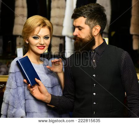 Man With Wallet And Girl With Happy Faces Among Coats