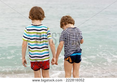 Two happy little kids boys running on the beach of ocean. Funny cute children, siblings, twins and best friends making vacations and enjoying summer on stormy rainy summer day. Miami, Florida.