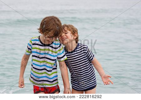 Two happy little kids boys running on the beach of ocean. Funny children, siblings, twins and best friends making vacations and enjoying summer on stormy rainy day. North sea. Family portrait