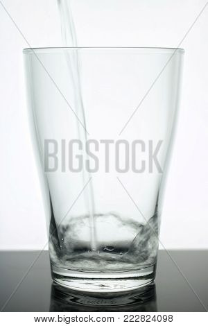 Glass Beaker Into Which Water Flows. Water Is Clean - Glass Is Transparent. Glass On A White Backgro
