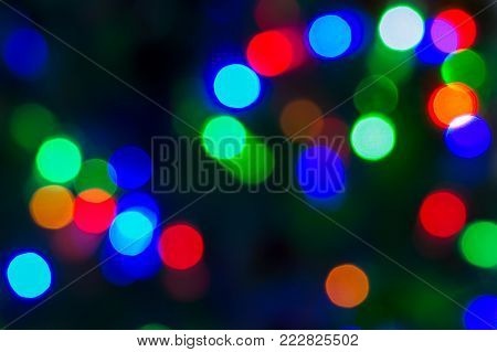 Holliday background. Christmas texture for your design and text. Multicolored bokeh on a dark background