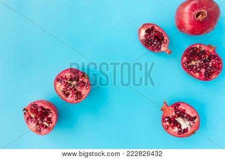 Whole, halved and quartered pomegranates on blue background with copy space. Top view.