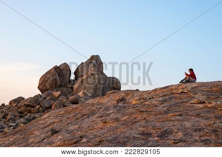 Woman sitting on rocks and looking at expansive view over the scenic Namib desert at dusk time. Travel in the Namib Naukluft National Park, Namibia, Africa.