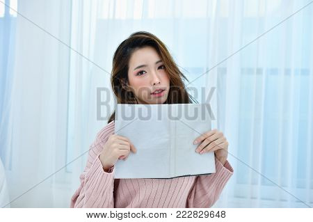 education Winter Concept. Cute Asian girl in winter dress. Beautiful woman is relaxing in a white bedroom. Beautiful women in winterwear are studying in the bedroom. Woman wearing a sweater in a white bedroom.