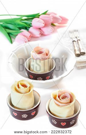 Puff pastry roses with ham and provola cheese in their casseroles, before being baked, on white table with pink tulips. Spring mood.