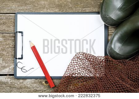 Fishing gear - fishing, pencil, hooks, boots, wooden background.