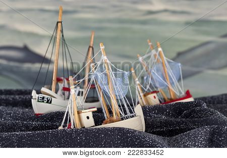 UMEA, SWEDEN ON NOVEMBER 27. View of toys, fishing boats on a spotted fabric material on November 27, 2014 in Umea, Sweden. Old school-painting as background. Illustrative editorial.
