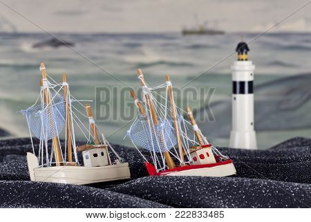 View of toys, fishing boats on a spotted fabric material. Old school-painting as background, beacon.