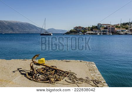 pier of the fiskardo village on the ionic sea close-up of ropes and anchor rusted on a pier in the bay of fyskardo the boats buildings and finally the mountains of the greek island of kefalonia