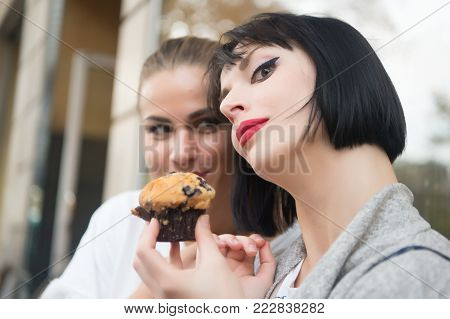 Girl friends with blueberry muffin in paris, france. Women look at cupcake in cafe. Hunger, temptation, appetite concept. Dessert, food, snack, pastry.