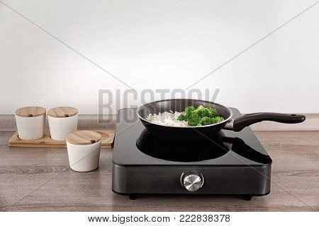 Frying pan with rice and broccoli on electric cooker in kitchen