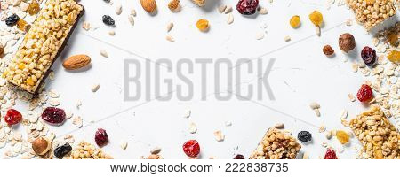 Granola bar and ingredients on a white stone table. Cereal granola bar with nuts, fruit and berries. Top view long banner format.