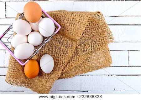 Top view of chicken eggs in metal shopping basket on checkered tablecloth on white wooden background.