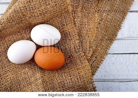 Top view of chicken eggs on checkered tablecloth on white wooden background.