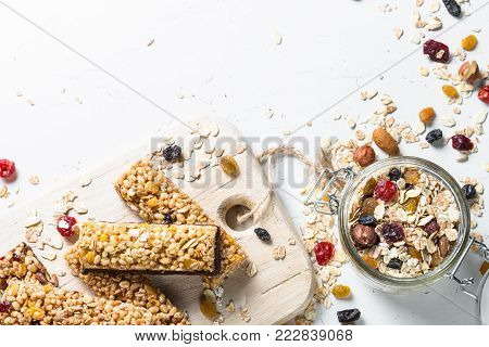 Granola bar with nuts, fruit and berries on a white stone table. Healthy sweet dessert snack. Top view copy space.