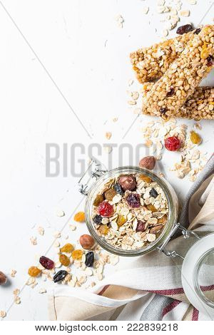Oat flakes or Granola with nuts, dry fruit and berries on a white stone table. Top view with copy space.