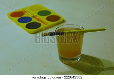 Paint brush on top of a water glass in focus and water-paint pallet in the background out of focus
