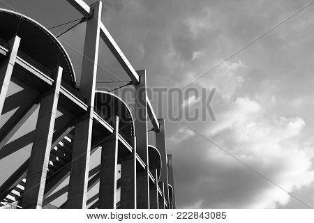 High architectonic vertical lines of a contemporaneous building (a sport arena) on a background of clouds the light filtered by clouds. A dynamic black & white image that makes us feeling small.