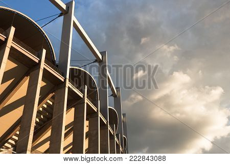 High architectonic vertical lines of a contemporaneous building (a sport arena) on a background of clouds beneath the light filtered by clouds. A dynamic image that makes us feeling small.