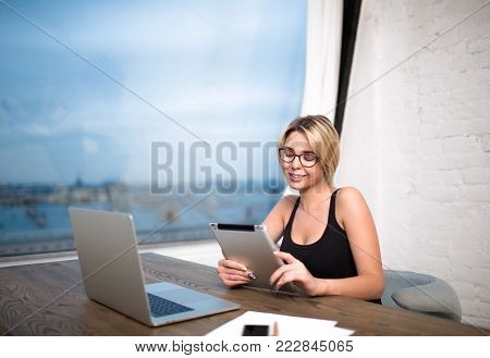 Female intelligent developer sites reading publication on touch pad, sitting at table with laptop computer during work day in company. Smiling businesswoman using digital tablet and portable net-book