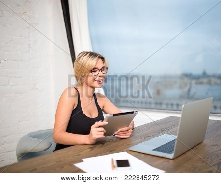 Woman smart secretary holding touch pad and reading financial documents on laptop computer, sitting at work table near office window. Female associate web editor using digital tablet and net-book