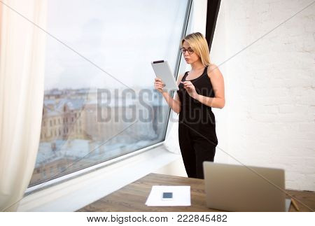 Young businesswoman reading information in internet on touch pad, after work on laptop computer, standing near office window with copy space. Female economist in glasses using portable digital tablet