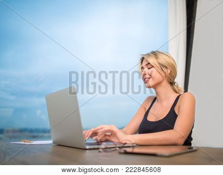 Young female manager keyboarding text on website via portable net-book, sitting near office window with copy space. Smiling hipster girl chatting in social network via modern laptop computer