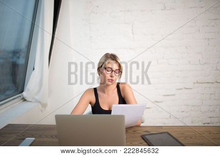 Young woman smart student reading paper documents, preparing to university lesson using net-book. Female in glasses skilled manager reading summary, sitting in office interior