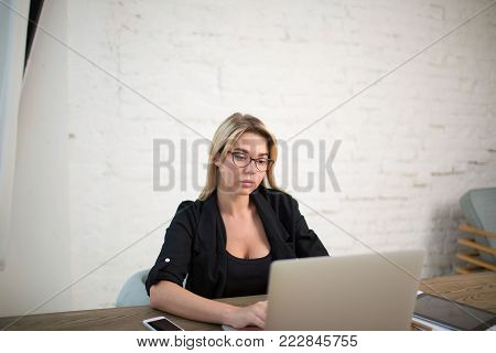 Businesswoman working on laptop computer, sitting in office interior. Female experienced broker using net-book. Skilled copywriter using notebook for research information