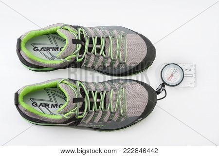 Brnenec, Czech Republic-July 9,2017: Men´s shoes Garmont 9.81 speed II for trail running, fast climbing, hiking and magnetic compass on white background.