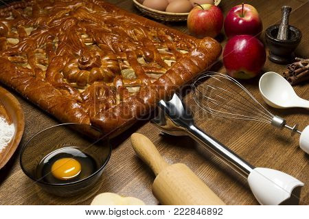Apple pie with baking ingredients, spices and kitchen tools for cooking, rustic homemade sweet food on wooden table, selective focus