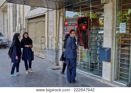 Isfahan, Iran - April 24, 2017: Two girls of school age, dressed in an Islamic school uniform with a forced hijab, are waiting for the street ATM to be vacated.