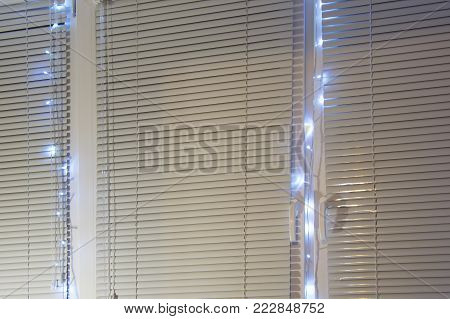 Window closed blinds decorated with shining electric garland. Blue lights between plastic roller shutters