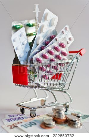 Czech health care and medicine - various pill and tablets in a shopping trolley and Czech crown currency