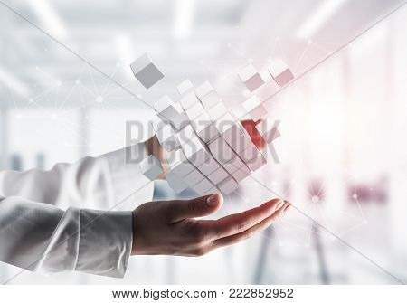 Cropped image of businessman hands holding multiple white cubes in hands with sunlight on office background. Mixed media.