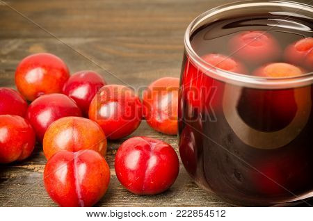 Ripe plum fruit (Julee) and juice on wooden background, healthy food